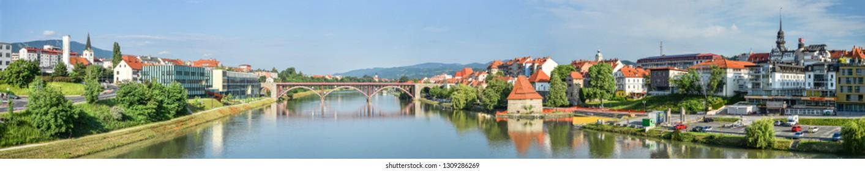 Maribor, Slovenia - May 20, 2018: Panorama of Maribor city, Slovenia. Drava River, buildings and Alps mountains of Maribor.