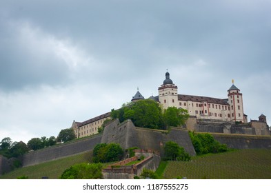 Marienberg Fortress, in Wurzburg, Germany, is surrounded by a wall on top of a hill. Behind is an overcast sky. The hill is covered with vineyards.