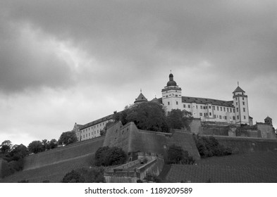 Marienberg Fortress, Wurzburg, sits on top of a hill, surrounded by vineyards. The sky is overcast. The photograph is in black and white.