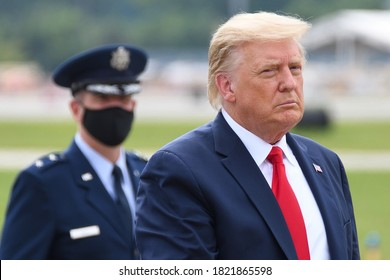 "MARIETTA, GA- SEPTEMBER 25, 2020: President Donald Trump walks to ""The Beast"" limousine with Air Force Major General John P. Healy in the background wearing a face mask at Dobbins Air Reserve Base."