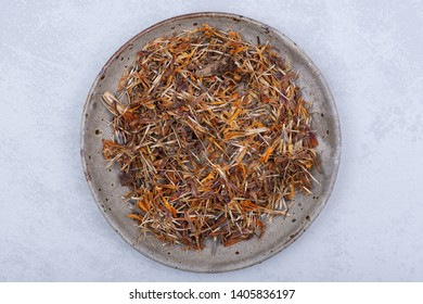 Marigold Dry Seeds (Mexican marigold, Aztec marigold, African marigold) in ceramic plate on gray  background. Tagetes erecta. Daisy family.