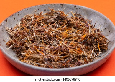 Marigold Dry Seeds (Mexican marigold, Aztec marigold, African marigold) in ceramic plate on orange background. Tagetes erecta. Daisy family.