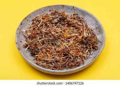 Marigold Dry Seeds (Mexican marigold, Aztec marigold, African marigold) in ceramic plate on yellow background. Tagetes erecta. Daisy family.