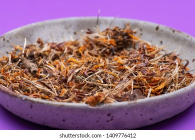 Marigold Dry Seeds (Mexican marigold, Aztec marigold, African marigold) in ceramic plate on purple background. Tagetes erecta. Daisy family.
