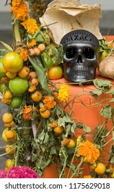Marigold flowers, fruit and food offerings on traditional altar with black clay handicraft skull for Day of the Dead festival, Oaxaca, Mexico