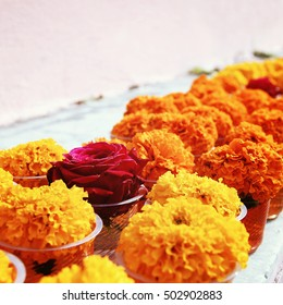 Marigold and rose for offering respect at Mahabodhi Temple. Aged photo. Colorful flowers on the white shelf. Bodhgaya, India.