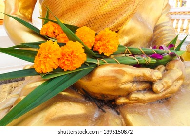 Marigolds placed on the buddha statue which sacrificial offering of Vesak Day festival for Buddhism time