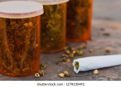 Marijuana bottled for medical use with joint on a stone table