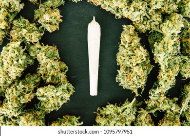 marijuana bud flowers of cannabis. grinder and shredded cannabis joint and a packet of weed on a black wood background close up