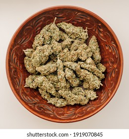 Marijuana buds in brown clay dish, flat lat, top view. Cannabis flowers and sweets on white background. Hemp recreation, pastime, legalization concept.