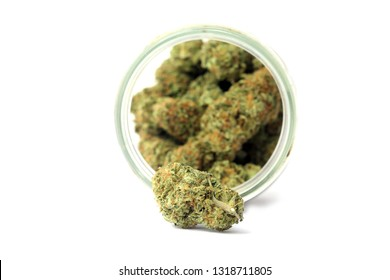 Marijuana. Marijuana Buds in a glass stash jar. Isolated on white. Room for text. Shallow depth of filed. Focus on front Cannabis Flower Bud.