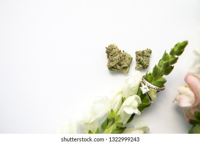 Marijuana Buds next to Pink White Flower with Diamond Wedding and Engagement Ring - Cannabis Wedding