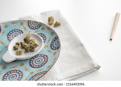 Marijuana Buds on a Vintage Plate atop a Silver Placemat and White Background With a Joint Minimalist Cannabis