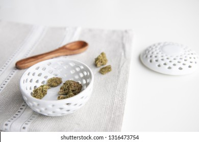 Marijuana Buds in a Porcelain Bowl on a Silver Placemat with Wooden Spoon and Lid - Minimalist Cannabis