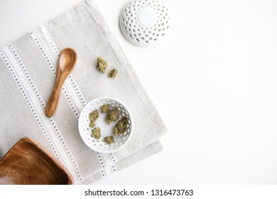 Marijuana Buds in a Porcelain Bowl on a Silver Placemat with Wooden Spoon, Bowl and Lid Top Down View - Minimalist Cannabis