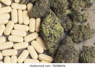 Marijuana buds and prescription pills on table. Macro close up, with 50/50 split between cannabis and pills.