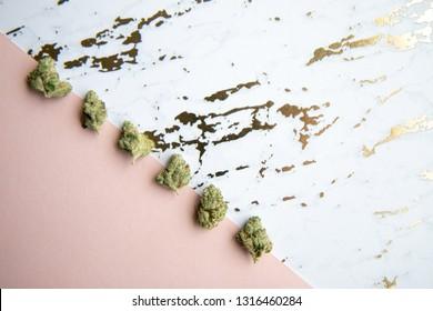 Marijuana Buds sit diagonally on Pink and Gold Marble Background Minimalist Cannabis