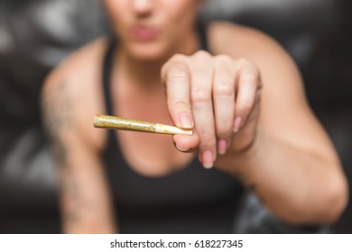 Marijuana or cannabis joint in a young woman's hand.