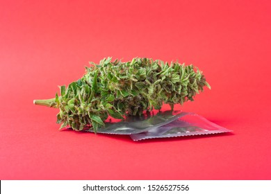 marijuana and condoms on red background,contraception for intercourse with cannabis,natural aphrodisiac.