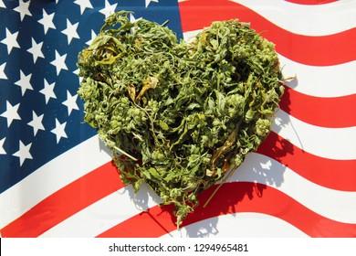 Marijuana. Dried Marijuana Leaves and Flowers in a Heart Shape. Cannabis or Ganja in a Heart Shape on an American Flag background.