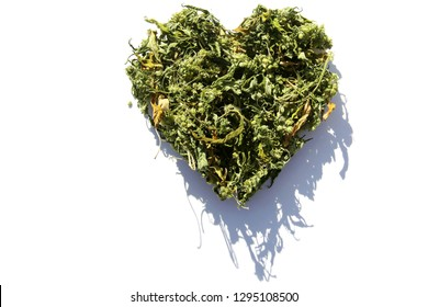 Marijuana. Dried Marijuana Leaves and Flowers in a Heart Shape. cannabis leaves in a heart design with shadow. isolated on white. room for text.