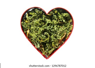 Marijuana. Dried Marijuana Leaves and Flowers in a Heart Shape. Ganga in a Red Heart Shape Cookie Cutter. Room for Text. Isolated on white. Text reads