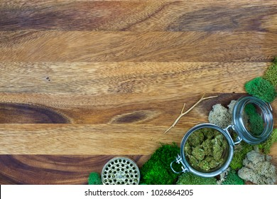 Marijuana in glass jar surround by green moss with wooden background