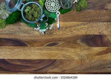 Marijuana in glass jar surrounded by moss, grinder and cleaning tool with wooden background