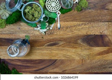 Marijuana in glass jar surrounded by moss, grinder, cleaning tool and bong with wooden background