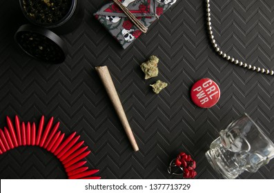 Marijuana joint and buds against a chevron black background with accessories