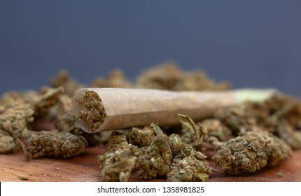 Marijuana joint and buds on a wooden table.