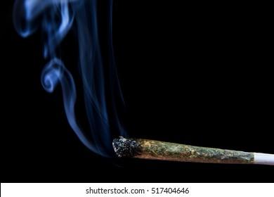Marijuana joint with smoke on black background