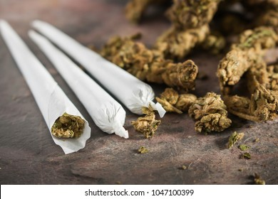 marijuana joints and buds on a stone table