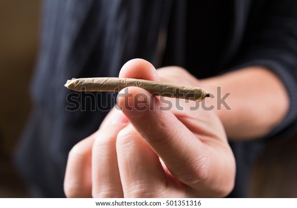 Marijuana joints in the mans hand. Man offering drugs