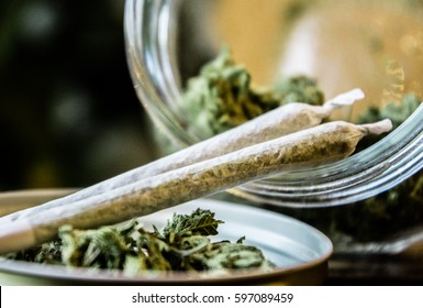 Marijuana Joints Next to a Jar