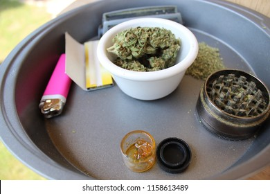 Marijuana kit of buds, rolling papers, rolling machine, lighter and grinder.