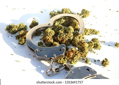 Marijuana Laws. Marijuana Buds with Police Hand Cuffs. Isolated on white. Room for text. Cannabis and the Law. Legalize it!