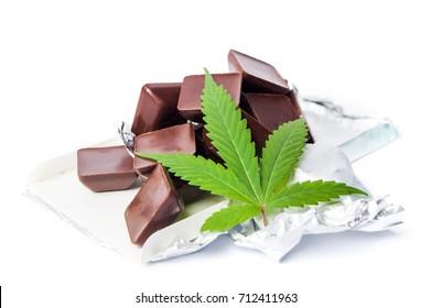 Marijuana leaf with chocolate cubes on white background