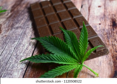 Marijuana leaf and chocolate on brown wooden background