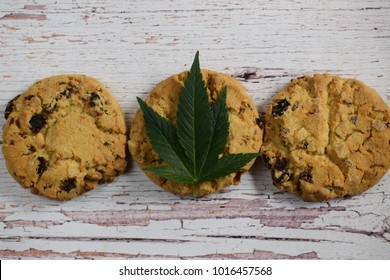 Marijuana leaf and cookie on white wooden backround