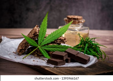 Marijuana leaf edible cannabis with CBD and cereal crunchy food multigrain chocolate, Thai hemp, and oil extracted canabis on brown wooden background.