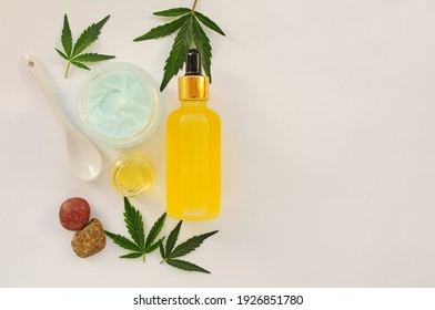Marijuana leaves, cbd oil, cosmetic cream. Fresh cannabis leaves close up, isolated on white background. Home relaxation, spa recreation, pastime therapy. Modern cosmetology.