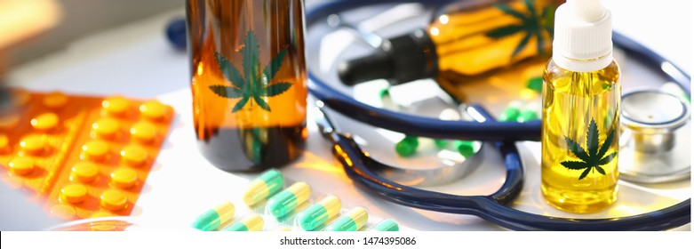 Marijuana oil medicinal pills with stethoscope on doctor office table.