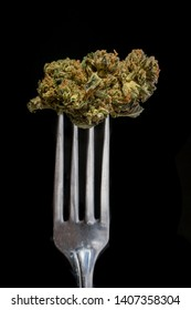 Marijuana is on a fork in a concept about marijuana edibles and food.