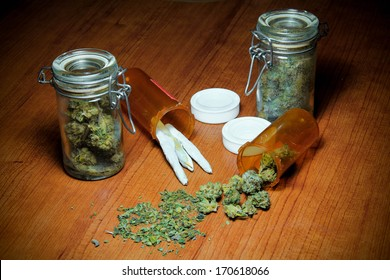 Marijuana On Table. Marijuana on a wood table. In piles, jars, prescription bottles and rolled into joints.