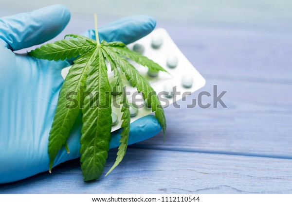 Marijuana and pills. Leaf of hemp and packing of tablets.