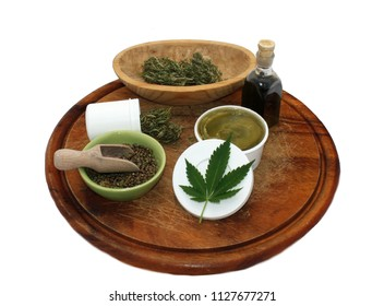 Marijuana products, cannabis tincture, dry weed buds, seeds, hemp salve on wooden desk isolated on white