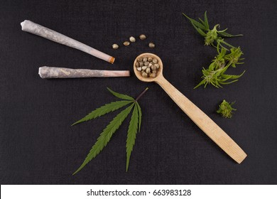 Marijuana seeds in wooden spoon with joints, buds and leaves from above. Alternative medicine.