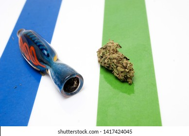 marijuana, small glass cannabis pipe and bud on colorful background