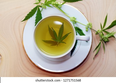 Marijuana Tea. Hemp Tea. Cannabis Tea in a White Tea Cup with a Marijuana Leaf and Stem with Flowers and Leaves on a Wooden Tree Stump serving tray. Room for text.
